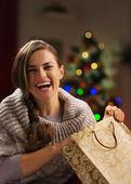 Mulher sorridente com saco de compras na frente da árvore de natal — Foto Stock