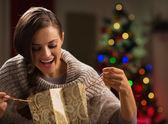 Mulher sorridente na frente da árvore de natal olhando numa sacola de compras — Foto Stock