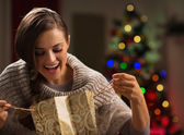 Smiling woman in front of Christmas tree looking in shopping bag — Stock Photo