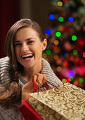Smiling woman with shopping bag in front of Christmas lights — Stock Photo