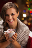 Smiling woman holding cup of hot chocolate with marshmallows — Stock Photo
