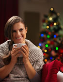 Happy young woman with cup of hot chocolate in front of Christma — Stock Photo