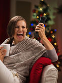 Excited young woman with cup of hot beverage looking TV — Stock Photo