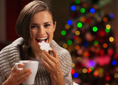Happy woman eating Christmas cookie and drinking hot chocolate — Stock Photo