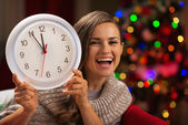 Happy woman showing clock in front of Christmas tree — Stock Photo