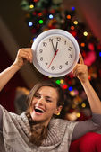 Cheerful woman showing clock in front of Christmas tree — Stock Photo