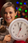 Portrait of smiling woman showing clock in front of Christmas li — Stock Photo