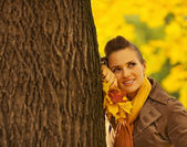Dreaming woman with fallen leaves leaning against tree — Stock Photo
