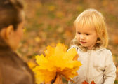 Mother showing baby fallen leaves — Stock Photo