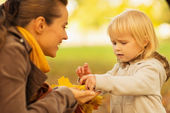 Mother showing baby fallen leaves and chestnuts — Stock Photo