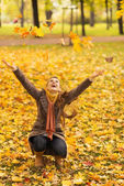Happy woman squatting and throwing fallen leaves — Stock Photo