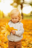 Baby holding fallen leaves — Stock Photo