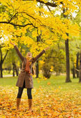 Happy woman throwing fallen leaves — Stockfoto