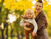 молодая мать, играя с младенца на открытом воздухе — Стоковое фото