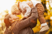 Young mother rising baby up — Stock Photo