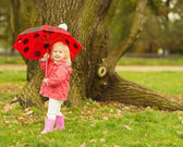 Happy baby with red umbrella outdoors — Stock Photo
