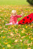 Baby with red umbrella collecting fallen leaves — Stock Photo