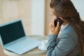 Donna d'affari parlando cercando nel portatile e mobile. vista posteriore — Foto Stock