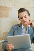 Thoughtful business woman looking in tablet PC — Stock Photo