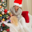Mother looking on baby decorating Christmas tree — Stock Photo