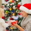 Baby girl presenting mother Christmas gift — Stock Photo