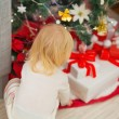 Baby taking Christmas present from under Christmas tree. Rear vi — Stock Photo