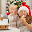 Happy mother and baby eating Christmas cookies — Stock Photo #16776417