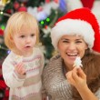 Smiling mother and baby eating Christmas cookies — Stock Photo