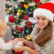 Happy mother giving baby Christmas cookies — Stock Photo