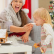 Mother giving bite Christmas cookies to baby — Stock Photo