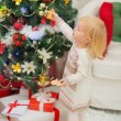 Stock Photo: Eat smeared baby eating Christmas cookies near Christmas tree