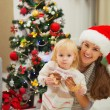 Portrait of mother and eat smeared baby near Christmas tree — Stock Photo