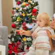 Eat smeared baby and mother near Christmas tree looking on copy — Stock Photo