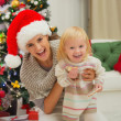 Portrait of laughing mother and eat smeared baby near Christmas — Foto de Stock