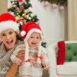 Portrait of mom and eat smeared baby girl in Christmas hats near — Stok fotoğraf