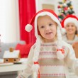 Stock Photo: Portrait of eat smeared baby girl in Christmas hats dancing