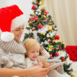 Happy mother and kid using tablet PC near Christmas tree — Stock Photo
