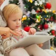 Mother showing baby something in tablet PC near Christmas tree — Stock fotografie #16776715