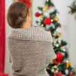 Woman looking on Christmas tree. Rear view — Stock Photo