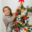Happy young woman hanging Christmas top on Christmas tree — Foto de Stock