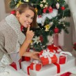 Womputting present box under Christmas tree and showing shh g — Stock Photo #16777697
