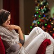 Calm young woman relaxing on chair in front of Christmas tree — Foto de Stock