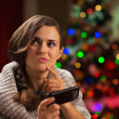 Thoughtful young woman writing sms in front of Christmas tree — Stock Photo