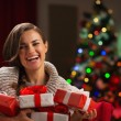 Happy young woman holding Christmas present boxes — Stock Photo #16778035