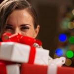 Girl hiding behind Christmas present boxes — Stock Photo #16778045