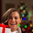 Happy young woman looking out from Christmas gift boxes — Stock Photo #16778055