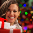 Happy young woman holding Christmas gift boxes — Stock Photo