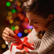 Happy young woman sitting chair and opening Christmas present bo — Foto de Stock