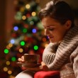 Stock Photo: Dreaming young womsitting chair with hot chocolate in front o