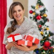 Royalty-Free Stock Photo: Portrait of smiling woman with present boxes near Christmas tree